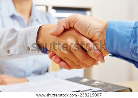 Business handshake in office as symbol for partnership and teamwork - stock photo