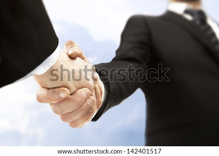 business handshake on sky background - stock photo