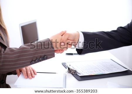 business handshake  sitting at the desk on office background, copy space area at the left upper corner - stock photo