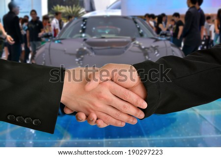 Business handshake with car exhibition background - stock photo