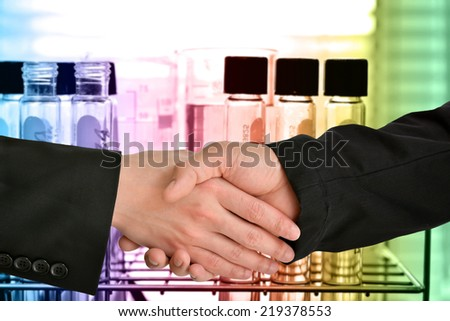 Business handshake with test tubes in laboratory background - stock photo