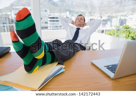 Business having a nap with feet over a pile of documents on his desk - stock photo