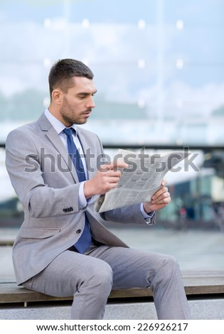 business, hot drinks and people and concept - young serious businessman with newspaper over office building - stock photo