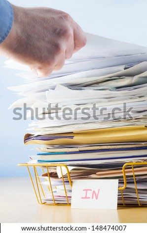 Business image of a male hand with blue shirt cuff visible, adding or removing document from tall pile in overflowing office In tray. - stock photo