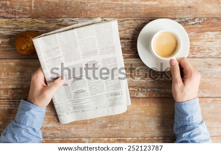 business, information, people and mass media concept - close up of male hands with newspaper, muffin and coffee cup on table - stock photo