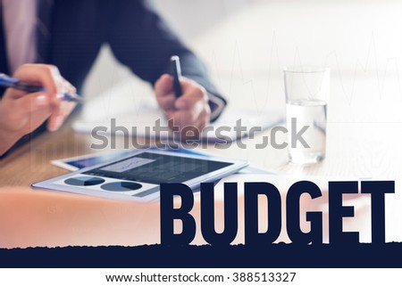 Business interface with graphs and data against business people using tablet - stock photo