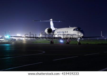 Business jet starting up at night. - stock photo
