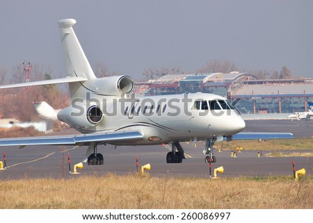 Business jet taxiing to the runway in the airport - stock photo