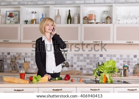 Business Lady in Office style Clothes - black Jacket and Pants white Shirt cooking Vegetables at Home Kitchen interior and holding Telephone and talking - stock photo