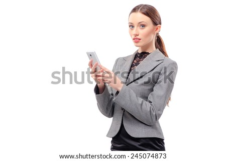 Business lady with mobile phone. Cheerful young caucasian woman in formal wear holding mobile phone and smiling while standing isolated on white - stock photo