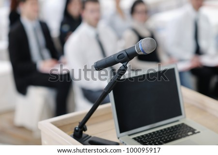business laptop and microphotone at podium on seminar conference education - stock photo