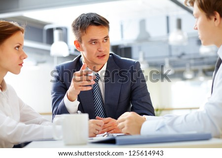 Business leader asking his employee about results - stock photo