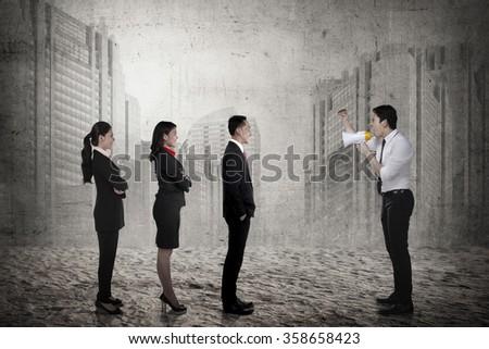 Business leader command his subordinate using megaphone. Business leadership concept - stock photo