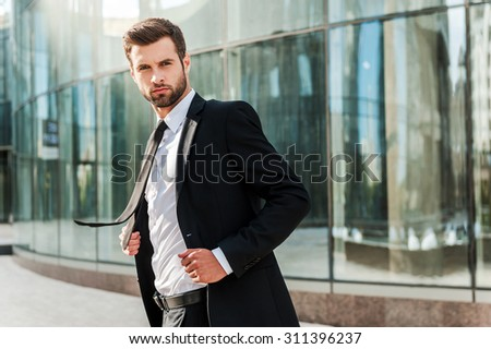 Business leader. Confident young businessman adjusting his jacket and looking at camera while standing outdoors with office building in the background - stock photo