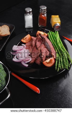 business lunch fresh roast beef meat slices on black plate wotj cutlery asparagus boiled broccoli rye bun on wooden table - stock photo