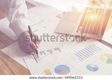 Business Male manager discussion ideas and writing business plan at workplace,man holding pens and papers for business data,notes documents,analysis chart at the table,vintage color,selective focus. - stock photo