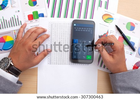 Business man analyzing financial statistics sitting at office desk using smart phone calculator - stock photo