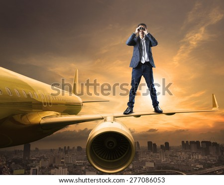 business man and binoculars lens standing on plane wing spying acting use for commercial competition and top secret strategy  - stock photo