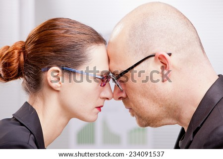 business man and business woman thinking that the one could beat the other - stock photo