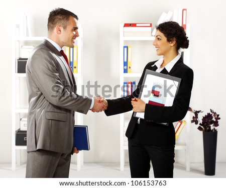Business man and business women in the office standing and handshaking - stock photo