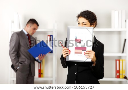 Business man and business women in the office working while she is blinking with her eye behind some charts - stock photo