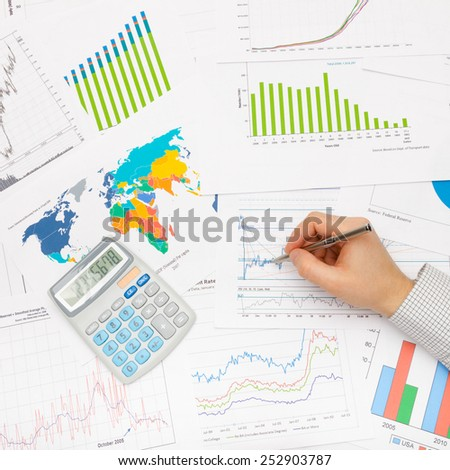 Business man and financial data - pen in hand - stock photo
