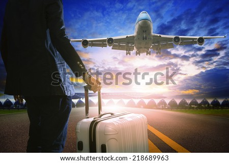 business man and luggage standing in airport and passenger jet plane flying over runway against beautiful sky use for air transport and travel by airline topic - stock photo