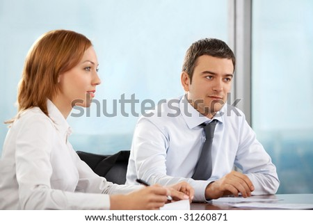 Business man and the woman at office look aside - stock photo