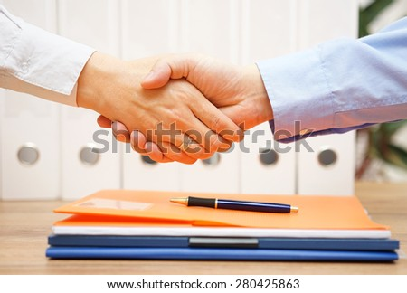 business man and woman are handshaking over documents in with office in background - stock photo