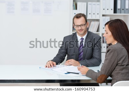Business man and woman in a meeting in the office sitting at a table discussing paperwork with copyspace alongside - stock photo
