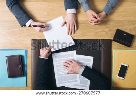 Business man and woman sitting at the lawyers's desk and signing important documents, hands top view, unrecognizable people - stock photo