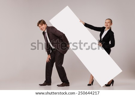 Business man and woman standing on both sides of blank banner the man holding it on his back.  isolated on grey background. Teamwork concept - stock photo