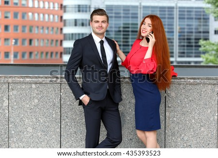 Business man and woman with phone in front of office building in the city - stock photo