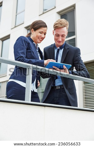 Business man and woman working on tablet PC outside the office in the city - stock photo