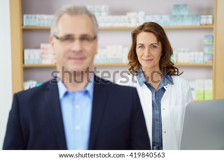 Business man at drug store standing at counter near female pharmacist besides shelf filled with medicine - stock photo