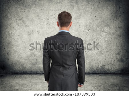 business man back view. Gray cracked wall - stock photo