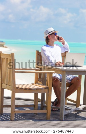 Business man calling by cell phone on white beach - stock photo