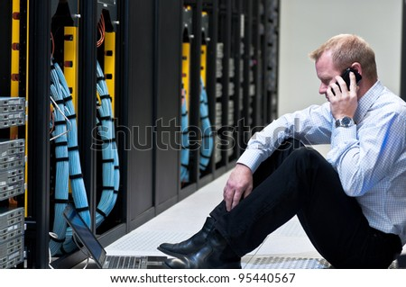 business man calling on a smartphone and looking at a laptop computer in a network data center - stock photo