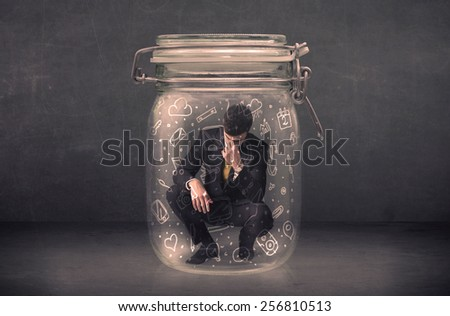 Business man captured in glass jar with hand drawn media icons concept on background - stock photo
