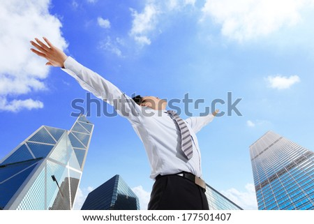 Business man carefree outstretched arms with sky and city background, asian - stock photo
