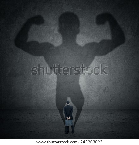 Business man casting a shadow of an athlete - business and career strength concept - stock photo