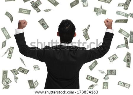 Business man celebrating in raining money, behind view - stock photo