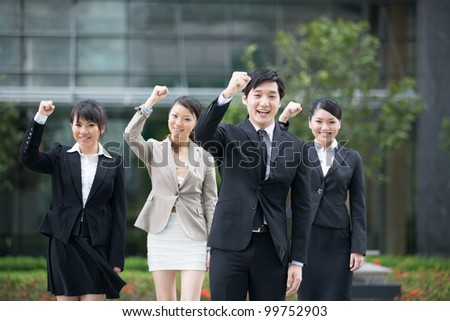 Business man celebrating with his team in the background. - stock photo
