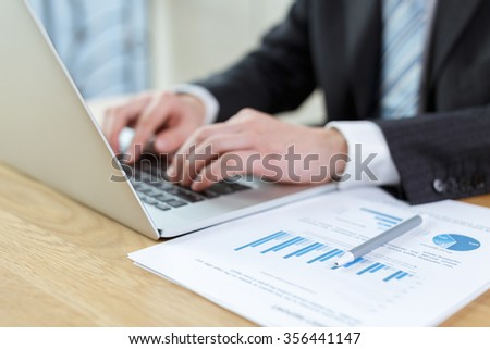 business man checking financial reports on table using computer,digital tablet and mobile phone - stock photo
