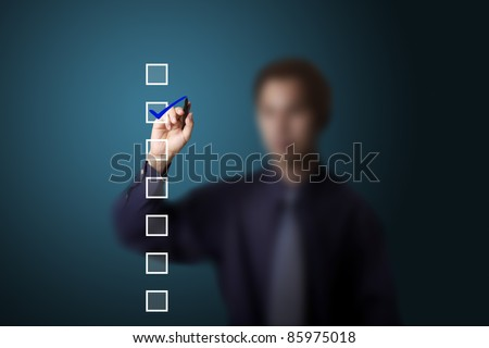business man checking on a checklist box - stock photo