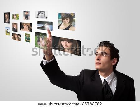 Business man choosing photos from digital gallery - stock photo