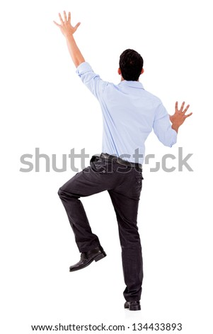 Business man climbing a wall - isolated over a white background - stock photo
