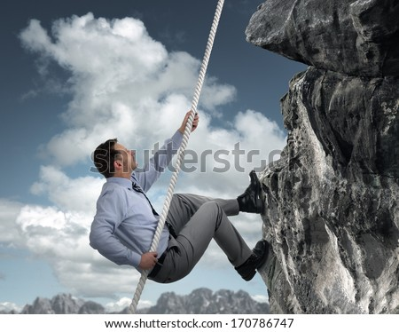 Business man climbs a mountain concept for challenge, conquering adversity and leadership - stock photo