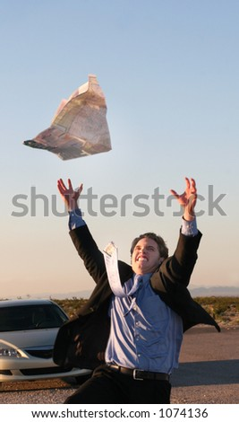 Business man consults map while being lost on the road in the middle of the desert - stock photo