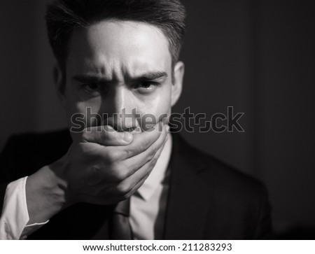 Business man covering his mouth - speak no evil concept. - stock photo